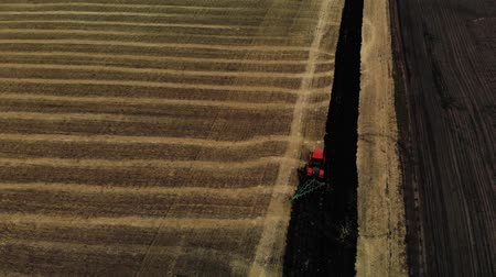Tractor plowing fields, preparing land for sowing. Red tractor. Aerial view. Farmer in tractor preparing land in farmlands. Tractor plows a field. Agriculture industry. Stock mozgókép