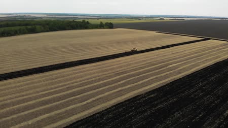 Tractors plowing fields, preparing land for sowing. Aerial view. Tractor plows a field. Agriculture industry.