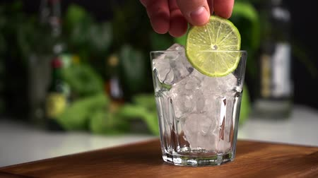 Man hand put lime in glass of ice cubes. Stock mozgókép