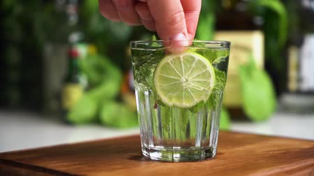 Man hand put lime in glass of soda or mineral water with mint.