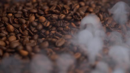 brazil : Slow motion coffee beans are roasted on a frying pan, smoke comes from coffee beans. Nice background with green plants and coffee pack.