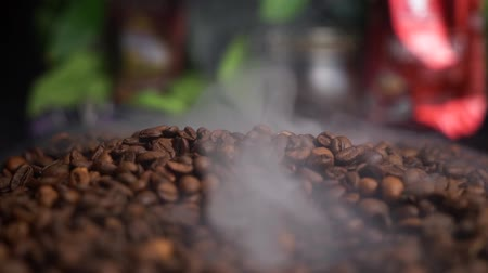 Slow motion coffee beans are roasted on a frying pan, smoke comes from coffee beans. Nice background with green plants and coffee pack.