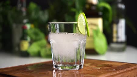 Ice cubes fall in glass of soda or mineral water slow motion with food background. Slice of lime on the glass.