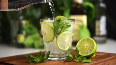 Slow motion mineral water or soda fill glass with lime, mint and ice cubes. Food background. Vidéos Libres De Droits