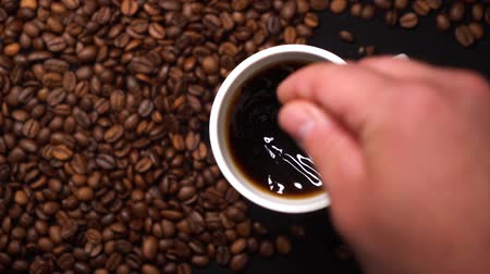 Person put sugar in white cup of black coffee and stirring coffee with a spoon. A lot of coffee beans on a black table. Slow motion.