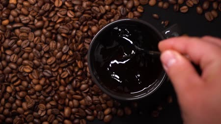 acorde : Person put sugar in black cup of black coffee and stirring coffee with a spoon. A lot of coffee beans on a black table. Slow motion.