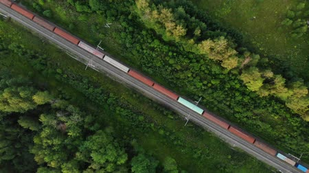 aerial view of a long freight train that goes along the tracks in the middle of the forest