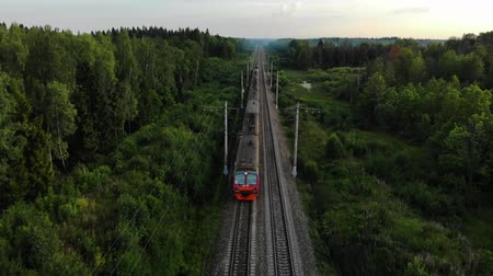 Aerial view: train at the rural scene in summer. The train rides through the rural countryside in the sunrise.