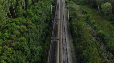 Aerial view of a train passing by on railway in the middle of nowhere. Fly above the train close up