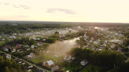 Aerial shot of beautiful countryside village in the morning sunlight, with mist floating on the farm land field. Cooking smoke curls up.