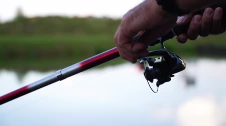 tyč : Close up rotation of the handle with a reel of fishing rod with lake on background. A man fishing on a big lake tightens a fishing line a reel of fish. Dostupné videozáznamy