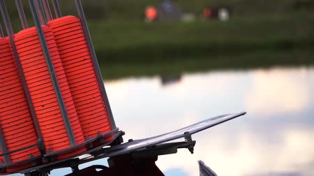 lupa : Slow motion view of throwing machine for clay pigeon shooting with orange plates near water