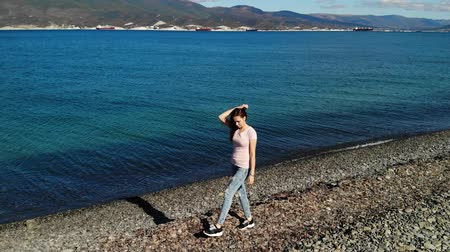 felnőtt : Girl in pink shirt and blue ripped jeans walking along beach and watch in camera. Aerial view