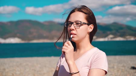 курильщик : Girl in pink shirt smoke electronic cigarette with sea and mountains on the background.