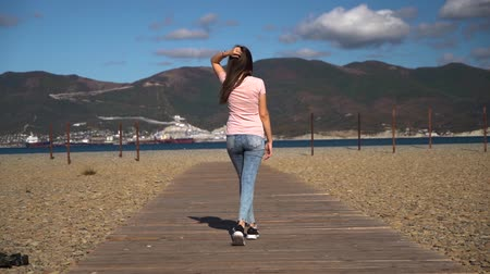 捨てる : Young and attractive girl or young woman in pink t-shirt walk away on wood path throw away jacket and turn around look in camera slow motion. 動画素材