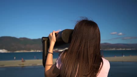 viewfinder : Traveler young woman in pink shirt and blue jeans watching through the coin stationary binoculars Stock Footage