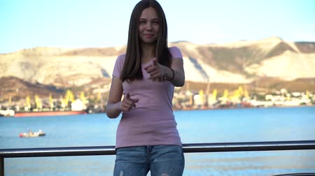 felkiáltás : Happy girl pointing fingers on you on embankment. Young woman in pink t-shirt pointing fingers in camera. Portrait of smiling girl. Stock mozgókép