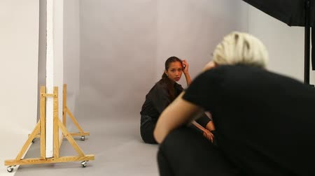 atirar : Photographer and model hold a photo session in the studio
