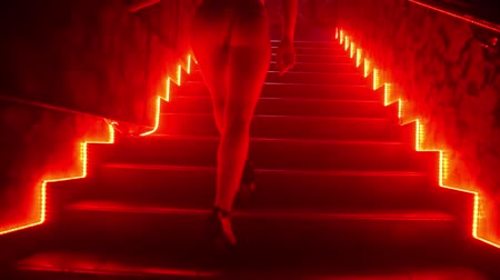 Dancer in sexy lingerie in a nightclub climbs the stairs Stock Footage