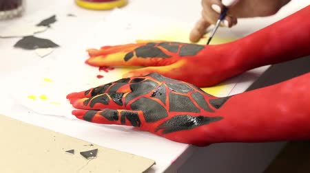 Girls paint their hands with paint. Body art. Close-up.