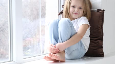 sill : The little girl is sitting on the windowsill with different emotions of the face.