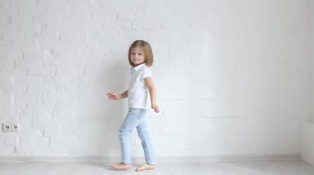Little girl runs along the white wall