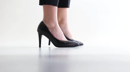 Girl in black shoes walks up in white studio