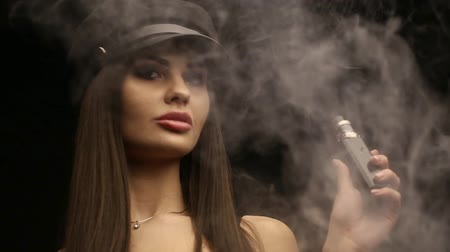 cartouche : Luxury brunette smokes vape in studio on black background Vidéos Libres De Droits