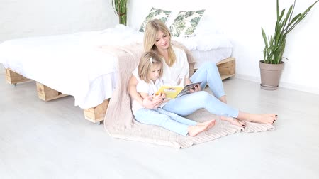 Happy mom and daughter in a bright studio. Sit reading a book.