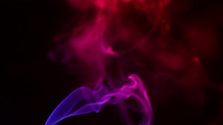 дымный : Multicolored smoke from aromatic sticks close up on black background