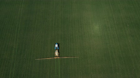 fertilizing : Aerial shot of a tractor on a green field.