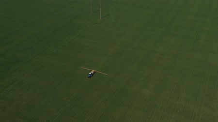 püskürtücü : Aerial shot of a tractor on a green field.
