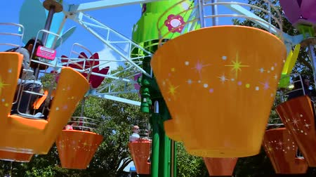 travel theme : Orlando, Florida. April 20, 2019.Parents and kids enjoying colorful flower pots Abbys Flower Tower on lightblue sky background at Seaworld in International Drive area (2) Stock Footage