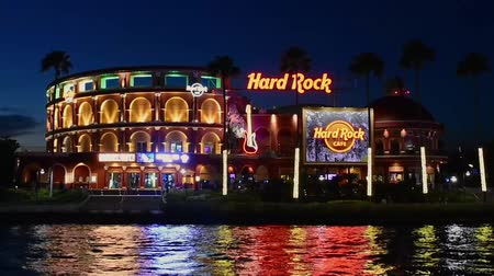 travel theme : Orlando, Florida. February 05, 2019. Panoramic view of colorful and illuminated Hard Rock Cafe on blue night background at Universal Studios area. Stock Footage
