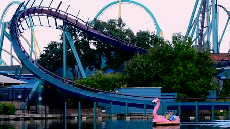 universal studios : Orlando, Florida. March 25, 2019 People enjoying ride on paddle swan boats at blue lake on Mako rollercoaster background in Seaworld Theme Park. Stock Footage