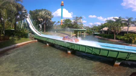 tampa bay : Tampa Bay, Florida. April 29, 2019. People enjoying Stanley Falls Flume on lightblue sky background at Busch Gardens. Stock Footage