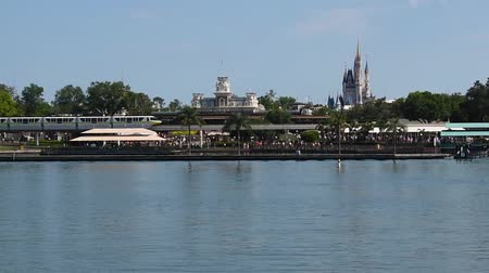 enjoynment : Orlando, Florida. May 23, 2019. Panoramic view of Monorail, Cinderella Castle, Main Street Station, and Seven Seas Lagoon from Ferry Boat. Stock Footage