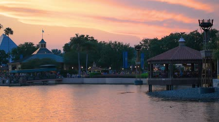 павильон : Orlando, Florida. May 29, 2019. People walking on boardwalk on beautiful sunset background at Epcot in Walt Disney World area.