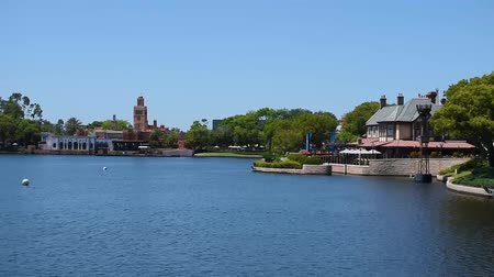 모터 보트 : Orlando, Florida. May 24, 2019. Time lapse of Morocco Pavilion and taxi boat sailing on blue lake in Epcot at Walt Disney World Resort area. 무비클립