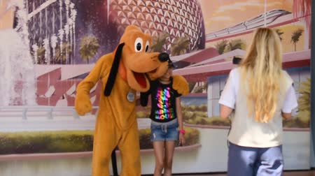 curto : Orlando, Florida. May 24, 2019. Female photographer taking photos to a nice family with Pluto in Epcot at Walt Disney World Resort area.