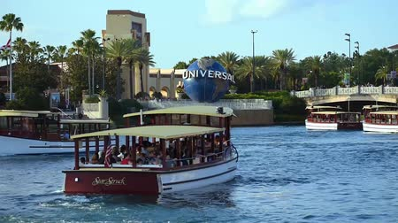 evrensel : Orlando, Florida. May 21, 2019. Panoramic view of Universal Studios arch, world sphere, palm trees and taxi boat in Citywalk at Universal Studios area. Stok Video