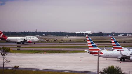 geçen : Orlando, Florida. June 03, 2019. Virgin Atlantic airplane gliding on the runway and partial view of American Airlines airplanes at Orlando International Airport.