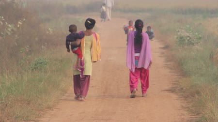 фронт : Indian women with children are on a rural road
