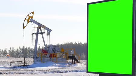 világosság : Billboard green screen on the background of oil pumps Stock mozgókép