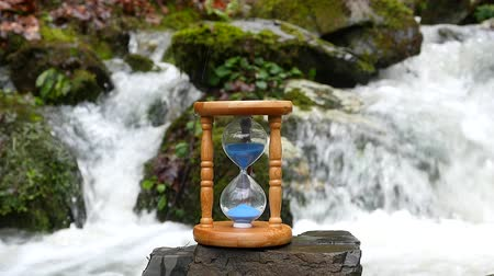 klepsydra : Hourglass on the background of a mountain stream