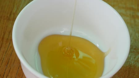 sobre o branco : Honey pour with a spoon in a Cup