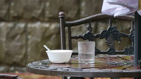 metro : Table and chairs in summer cafe under heavy rain
