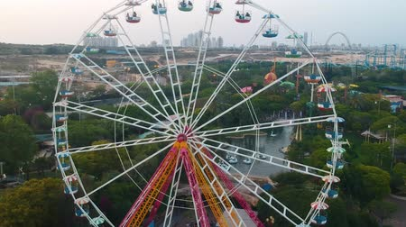 izrael : Superland, Rishon Lezion, Israel, June 3, 2019. Ferris wheel. A beautiful view from a drone flying near the observation wheel against the backdrop of a beautiful amusement park.
