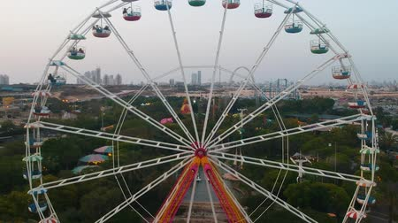 dev : Superland, Rishon Lezion, Israel, June 3, 2019. Ferris wheel. A beautiful view from a drone flying near the observation wheel against the backdrop of a beautiful amusement park.