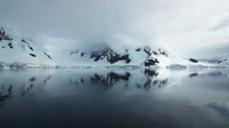 Антарктика : Moving Ice Floes and Ice Sheets in the calm Antarctic Sea, Reflection of Antarctica Mountain in water surface. Amazing beautiful views of Nature and landscape of snow, ice and white of Antarctic.